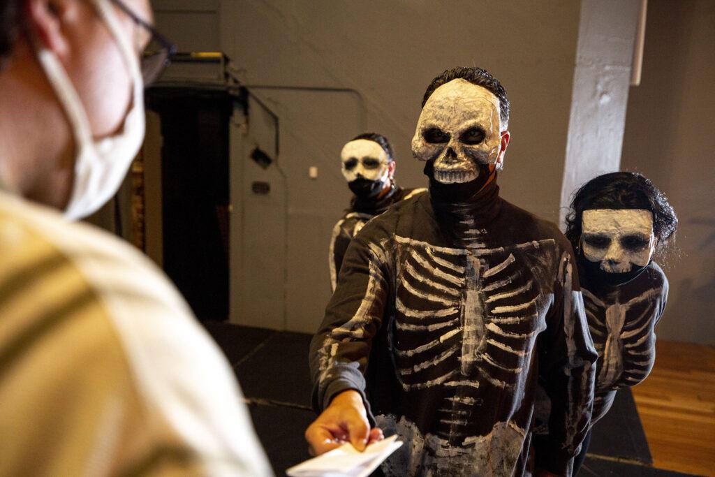 "Paul Zamora, leading a pack of La Muerte hands Davie Gonzalez a draft notice during a rehearsal of ""El Corrido del Barrio"" at Su Teatro. Sept. 15, 2021."