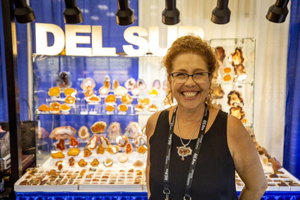Ana De Los Santos runs the Del Sur agate booth in the Denver Gem & Mineral Show's room in the larger Hardrock Summit at the Colorado Convention Cener, Sept. 16, 2021.