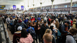 Passengers throng the Great Hall at Denver International Airport as they wait to pass through the south security checkpoint on Friday, October 22, 2021.