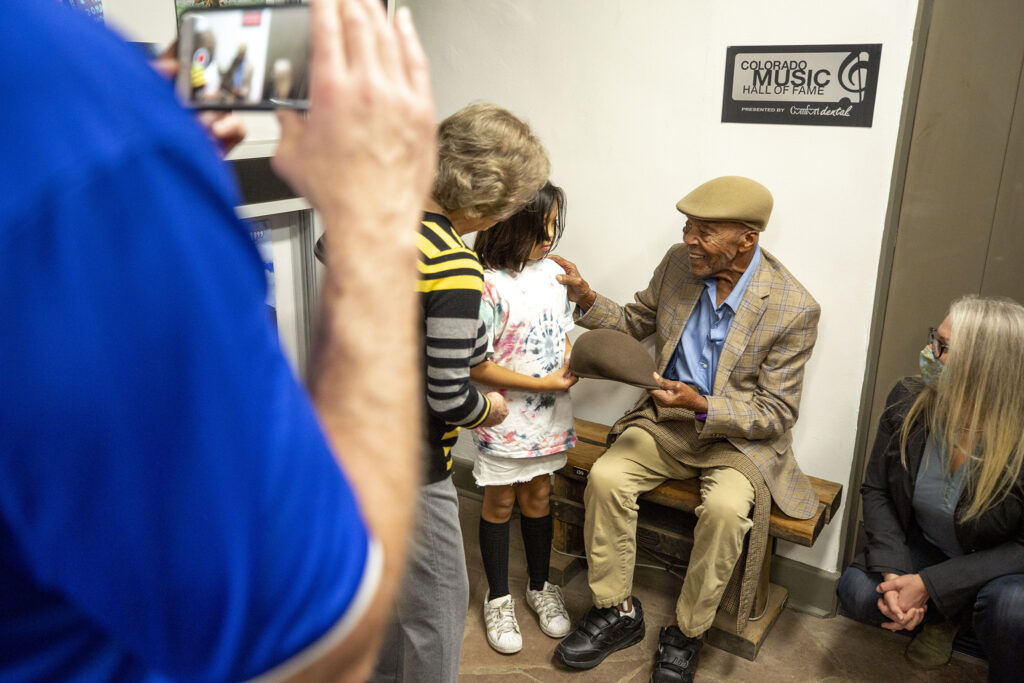 Charlie Burrell takes a Kangol hat from his great-granddaughter, Victoria, during a visit to the Colorado Music Hall of Fame. Oct. 2, 2021.