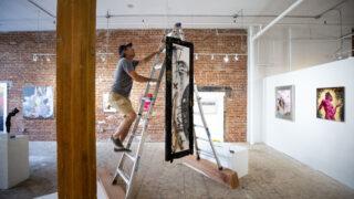 Brett Matarazzo tweaks a hanging piece made for Interplay – Art + Opera at the BRDG Project. Oct. 7, 2021.