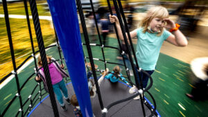 Bonnie (8) rides a fast-moving merry-go-round like a sea captain at the new City Park playground. Oct. 26, 2021.